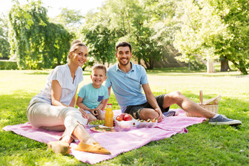 family, leisure and people concept - happy mother, father and little son having picnic at summer park