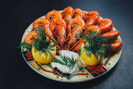 shrimps with lemon and black pepper on dark background