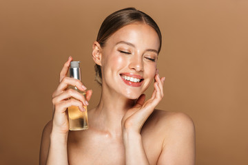 Image of adorable half-naked woman smiling at camera and holding face oil
