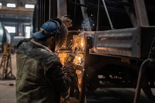 Welder repairs freight car in railway depot