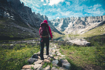 Woman hiker hiking on high altitude mountains Wall mural