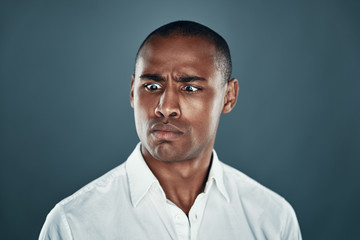 Cross eyed man. Handsome young African man in shirt making a face while standing against grey background