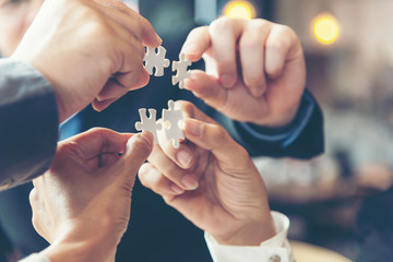 Businessman team work holding two jigsaw connecting couple puzzle piece for matching to goals target, success and start up new project in office, select focus. Business Concept. Wall mural