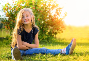 Smiling little blond girl with long hair sitting on the grass