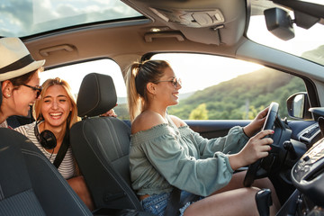 Three best female friends travel together.They drives a car and making fun.Summer vacation.