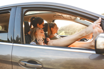 Three best female friends travel together.They drives a car and making fun.Summer vacation. Wall mural