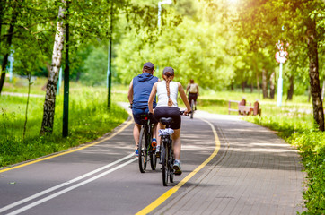 Cyclists ride on the bike path in the city Park  Wall mural