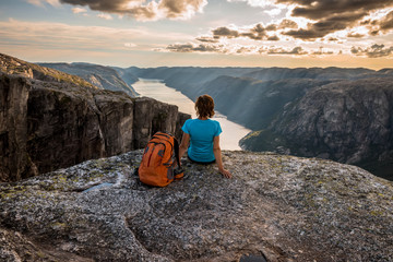 Sporty woman on the top of fjord near Kjeragbolten, Norway. Relax, success, motivation concept