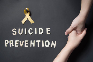 World suicide prevention day - Holding hands for helping and supporting depressed woman with yellow ribbon awareness and SUICIDE PREVENTION wooden word on black background. Mental health care concept.