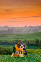 Miniature house on the grass at sunrise. Concept of Travel