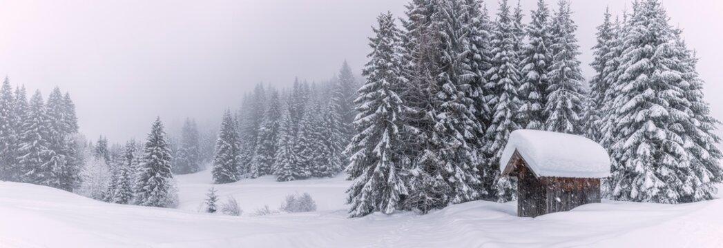 Panoramabild einer schneebedeckte Hütte in den Alpen