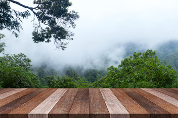 Wood old table against landscape mountain and fog background. For your product placement or montage with focus to the table top in the foreground