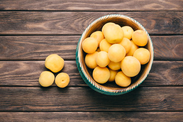 Fresh apricots in a wooden bowl.