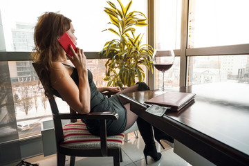 Obraz Young pretty woman sitting at a table in a cafe slowly drinking a glass of wine looking out the panoramic window with a beautiful view of the city and talking on phone - fototapety do salonu