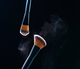 Make up brush with  powder explosion on black background