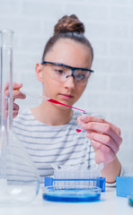 Teen girl student caring out experiments in chemistry class.