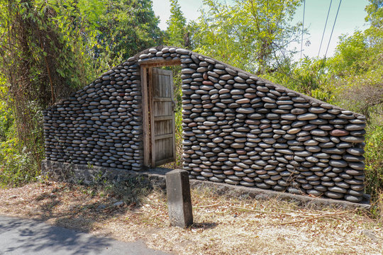 A boulder wall with open wooden doors. Stone wall by the road in Bali Island, Indonesia. Enter the jungle. Mystical place with mysterious building. Step into the unknown.