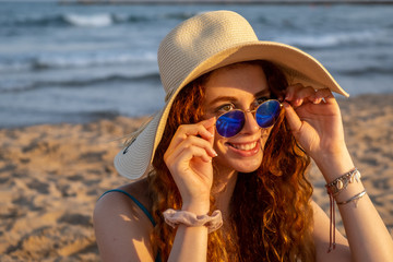Young redheaded girl wearing a hat and sunglasses on a Mediterranean beach.