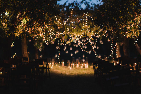 Coziness and style. Modern event design. Lounge zone and european traditional wedding ceremony decoration outdoors in the evening, decorated with candles and lights.