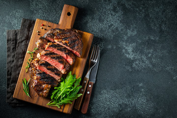 Wall Murals Steakhouse Sliced steak ribeye, grilled with pepper, garlic, salt and thyme served on a wooden cutting Board on a dark stone background. Top view with copy space. Flat lay