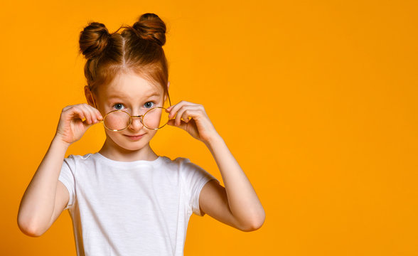 Beautiful young girl with red hair with a bagel in her stylish glasses looks at you in the frame.