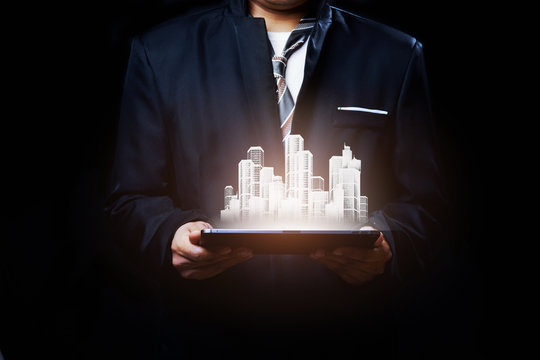 Real estate smart city and building technology on tablet. Present by businessman