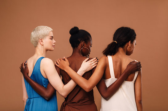 Three diverse women standing against brown background hugging each other