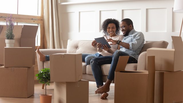 Happy african american couple use digital tablet on moving day