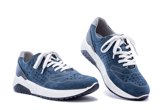 Close up of elegant light blue sports shoes in natural nubuck leather for adult men photographed on a white background. Fashion accessories.