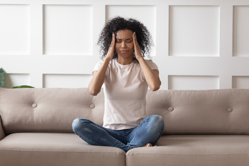 Upset stressed young african woman massage temples feel strong headache