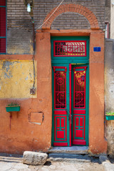 Old grunge decorated door painted in green and red vibrant colors on orange painted stone wall, Old Cairo, Egypt