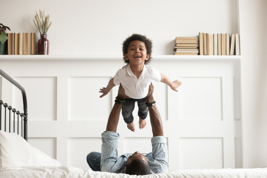 Happy african kid boy flying in fathers arms on bed