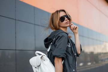 Modern pretty young hipster woman in a trendy gray jacket with a white stylish leather backpack in sunglasses on the street near a gray modern building on summer day. Urban girl model. Street fashion.