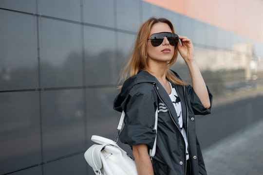 Red-haired young hipster woman in stylish jacket with vintage leather backpack is standing and straightening trendy sunglasses near modern building in the city on a summer day. Pretty beautiful girl.