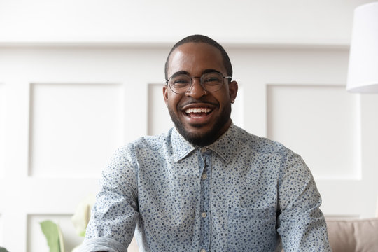 Happy black man video calling looking at camera at home