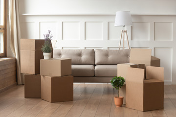 Moving day concept, cardboard boxes in modern house living room