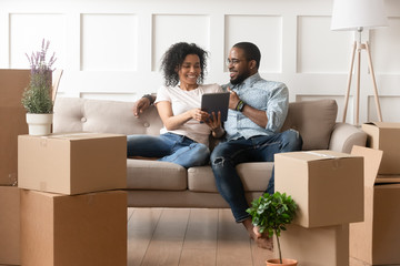 Smiling black couple use digital tablet on moving day