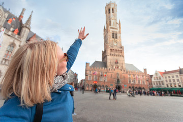 Autocollant pour porte Cracovie Young woman shows hand on Belfort Tower in Bruges, Belgium