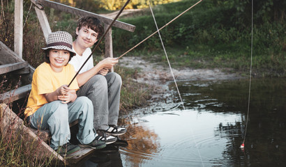 Happy boys go fishing on the river, Two children of the fisherman with a fishing rod on the shore of lake