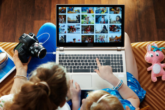 mother and child looks at photo collage on laptop