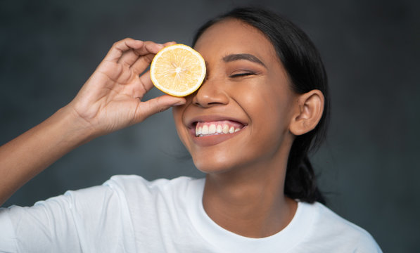 Portrait of beautiful young smiling woman in white t-shirt holding lemon slice in front of eye over concrete background