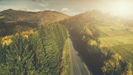 Aerial Mountain Road Scenery Landscape. Autumn Pine Tree Forest Scene View. Spruce Green Hill Valley Countryside. Sunset Cloud Sky. Wild Nature, Travel, Lifestyle. Cinema Drone Flight