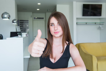 Close up Portrait of happy smiling young woman with deep decollete and thumb up hand sitting behind the desk in the office hall. Selective focus, copy space.