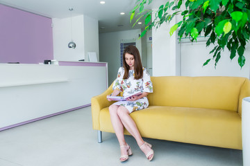 In full growth Portrait of Smiling young business woman sitting on the yellow sofa in the business hall and writing in notebook, makes notes of useful information, dressed elegantly. Copy space.