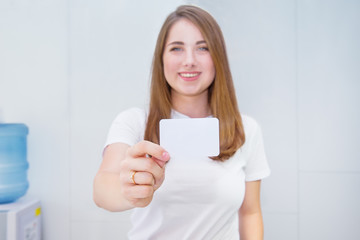Business card or gift card. Blurred Happy and excited caucasian woman in casual clothes showing focused blank empty paper card with copy space for your design on light indoor background.