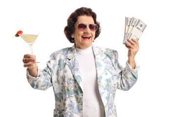 Happy senior woman holding cocktail and money