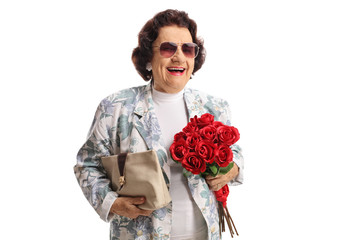 Cheerful elderly lady with a purse and a bunch of red roses smiling at the camera