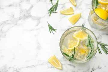 Glasses of refreshing lemonade on marble table, above view and space for text. Summer drink
