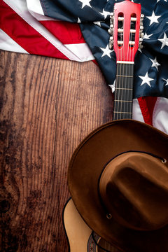 American culture, living on a ranch and country music concept theme with a cowboy hat, USA flag and acoustic guitar on a wooden background in a old saloon with copy space