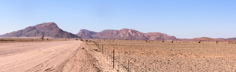 Gravel dirt road leading towards mountains in Central Namibia